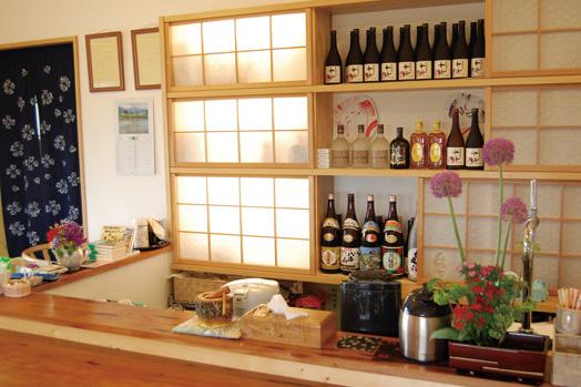 ケヤキの一枚板のカウンターの奥には、お酒がズラリ。オリジナルの芋焼酎や麦焼酎も