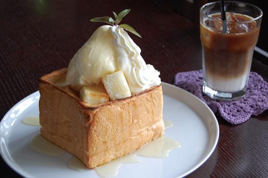 毎日焼き上げる手作り食パンに、アイスクリームとハチミツをたっぷり乗せた「ハニーアイストースト(680円)」。写真右奥は「アイスカフェオレ(520円)」です