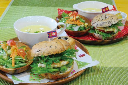 写真左手前は、3種類から選べるベーグルサンド(写真は塩鶏のテリヤキ)とノンオイルマフィンが付いた「ベーグルランチ(980円)」、右奥は2種類から選べるベーグルサンド(写真は卵&トマト)とゼリーの付いた「キッズベーグルサンド(580円)」。いずれも野菜スープ、ミニサラダ付き
