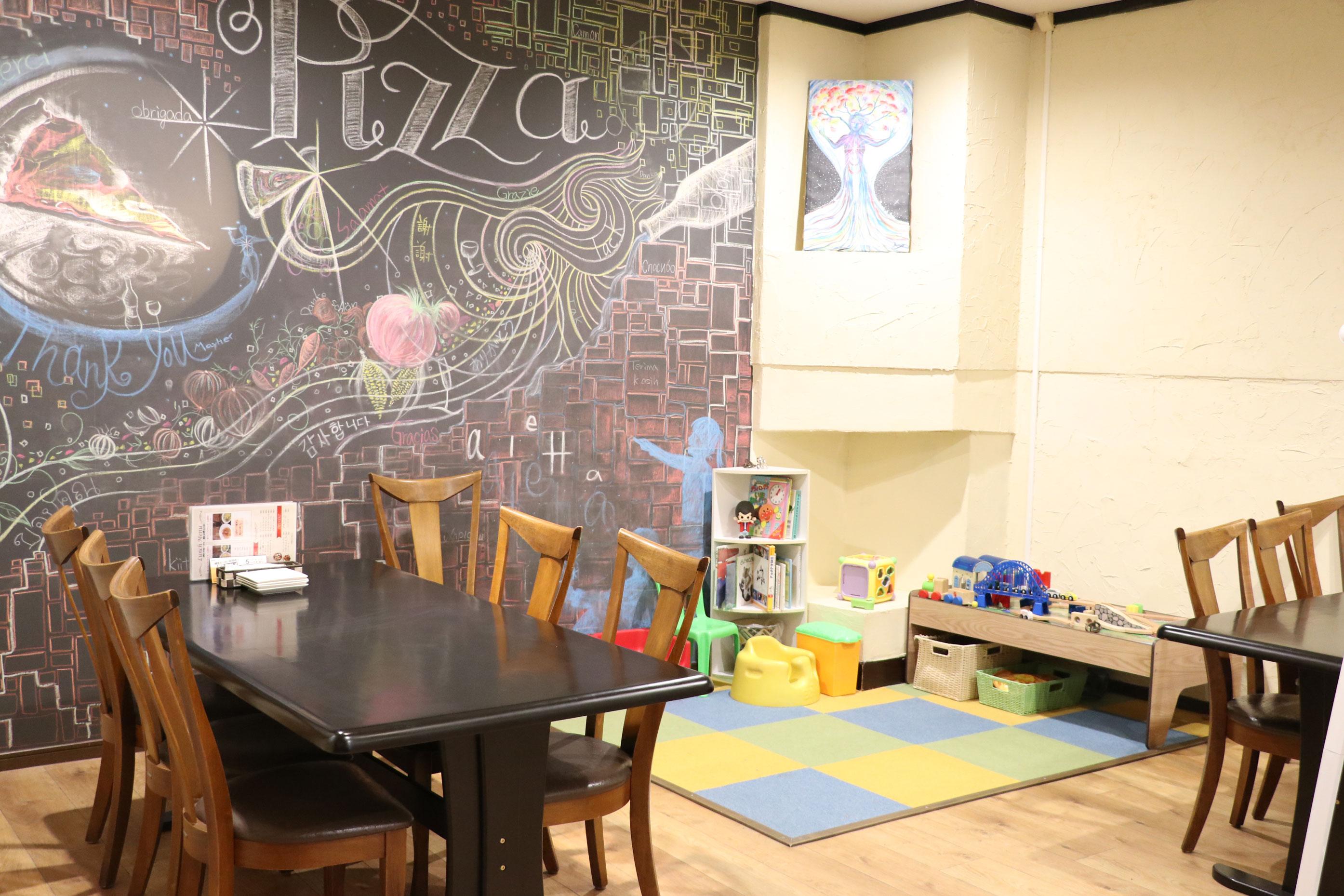 店内奥のキッズスペース。近くのテーブルは子連れ優先で案内しますが、予約も可能です。トイレにはおむつ替えスペースもあり