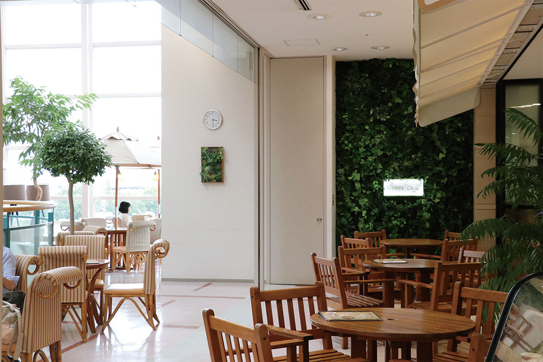 吹き抜けの天井も高く、開放的な店内。パラソルの備えられた明るいテラス席も人気です